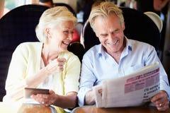Ältere Paare, die auf Zug-Reise sich entspannen Stockfoto