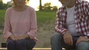 Ältere Paare, die auseinander auf Bankfreien, -täuschung, -Auseinanderbrechen und -groll sitzen stock video footage