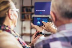 Ältere Paare, die bequem auf einem Sofa mit ihren Rückseiten holiding sind Fernsteuerungshauptsystem sitzen lizenzfreie stockbilder