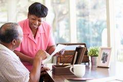 Ältere Paare, die Buchstaben in Andenken-Kasten setzen Lizenzfreies Stockfoto