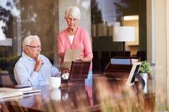 Ältere Paare, die Buchstaben in Andenken-Kasten setzen Stockfoto