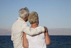 Ältere Paare, die das Meer überwachen Stockfotografie