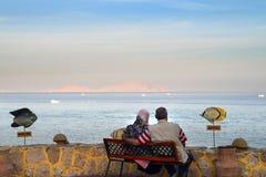 Ältere Paare, die das Meer umarmen und betrachten stockbild