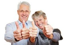 Ältere Paare, die Daumen hochhalten Stockbild
