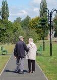 Ältere Paare, die in den Park schlendern Lizenzfreie Stockfotos