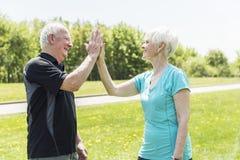 Ältere Paare, die in den Park tut hoch fünf laufen lizenzfreies stockfoto