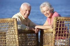 Ältere Paare, die in den Stühlen sich entspannen auf Strand sitzen Stockfotos