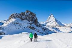 Ältere Paare, die den Winter wandert nahe Matterhorn, Zermatt tun Stockfotografie