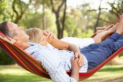 Ältere Paare, die in der Hängematte sich entspannen stockbilder
