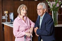 Ältere Paare, die an der Hotelaufnahme warten Lizenzfreie Stockfotos