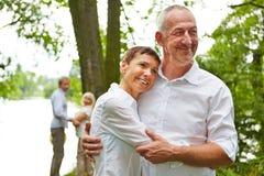 Ältere Paare, die in der Natur umfassen stockfotografie