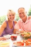 Ältere Paare, die draußen essen lizenzfreies stockfoto