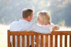 Ältere Paare, die draußen sitzen Lizenzfreies Stockbild