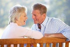 Ältere Paare, die draußen sitzen Lizenzfreie Stockfotos