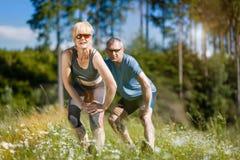 Ältere Paare, die draußen Sport tun Stockbilder