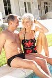 Ältere Paare, die durch im Freienpool sich entspannen Lizenzfreie Stockfotos