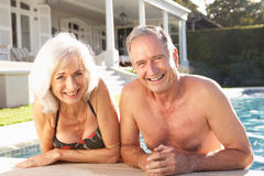 Ältere Paare, die durch im Freienpool sich entspannen Lizenzfreie Stockbilder
