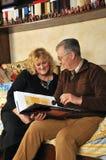 Ältere Paare, die ein Buch lesen Stockbild