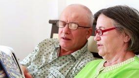 Ältere Paare, die ein Fotoalbum aufpassen stock footage