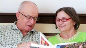 Ältere Paare, die ein Fotoalbum aufpassen stock video