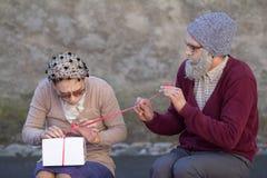 Ältere Paare, die ein Geschenk öffnen. Stockbilder