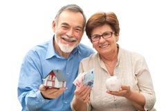 Ältere Paare, die ein Hausmodell und -Sparschwein halten Stockfotos