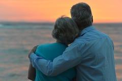 Ältere Paare, die ein Meer schauen stockfotografie