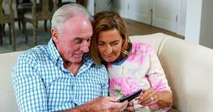 Ältere Paare, die ein selfie am Handy im Wohnzimmer nehmen stock video footage