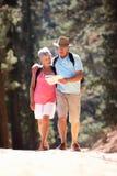 Ältere Paare, die eine Karte lesend gehen Lizenzfreies Stockbild
