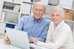 Ältere Paare, die an einem Laptop in einem Büro arbeiten Stockbilder