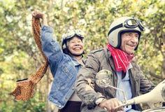 Ältere Paare, die einen klassischen Roller reiten stockfotos