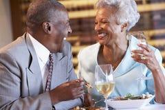 Ältere Paare, die an einer Gaststätte zu Abend essen lizenzfreies stockbild