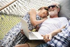 Ältere Paare, die in einer Hängematte sich entspannen lizenzfreie stockfotos