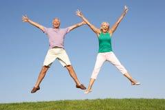 Ältere Paare, die in einer Luft springen lizenzfreie stockbilder