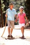 Ältere Paare, die entlang eine Landstraße gehen Lizenzfreies Stockbild