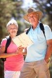 Ältere Paare, die entlang eine Landstraße gehen Stockfoto