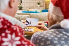 Ältere Paare, die Familien-Fotos auf Weihnachten betrachten lizenzfreie stockfotografie
