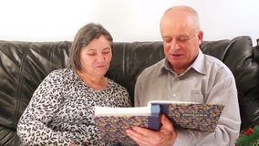 Ältere Paare, die Fotoalbum auf Weihnachten durchlaufen stock video