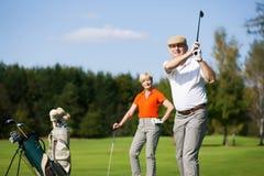 Ältere Paare, die Golf spielen lizenzfreies stockfoto
