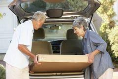 Ältere Paare, die großes Paket in Rückseite des Autos laden lizenzfreie stockbilder