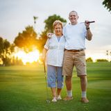 Ältere Paare, die heraus zusammen Porträt des Golfs spielen lizenzfreie stockfotos