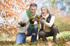 Ältere Paare, die Herbstblätter montieren Stockbilder