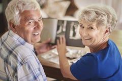 Ältere Paare, die ihre alten Fotos aufpassen Lizenzfreie Stockfotos
