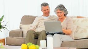 Ältere Paare, die ihren Laptop betrachten stock video