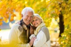 Ältere Paare, die im Herbstpark umfassen lizenzfreie stockbilder