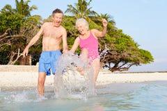 Ältere Paare, die im Meer auf tropischem Strandurlaub spritzen Stockbilder