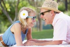 Ältere Paare, die im Sommer-Garten sich entspannen Lizenzfreie Stockfotos