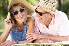 Ältere Paare, die im Sommer-Garten sich entspannen Stockbilder