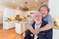 Ältere Paare, die innere kundenspezifische Küche umarmen Stockbilder