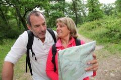 Ältere Paare, die Karte wandern und betrachten Lizenzfreie Stockfotografie